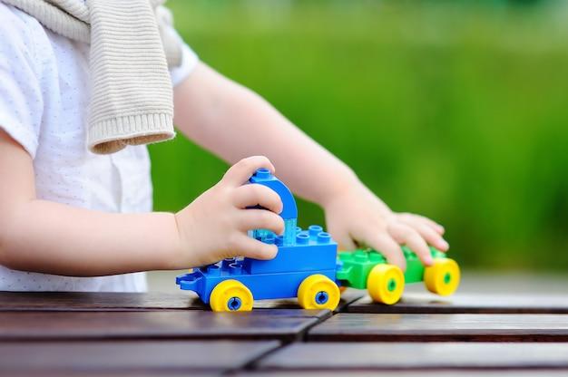 Kleinkindjunge, der draußen mit spielzeugzug am warmen sommertag spielt