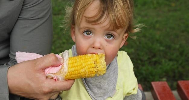 Kleinkindjunge, der mais auf der straße auf einem rasenhintergrund isst