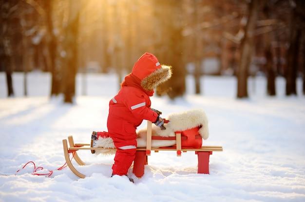 Kleinkindjunge, der spaß im winterpark hat. spiel mit frischem schnee