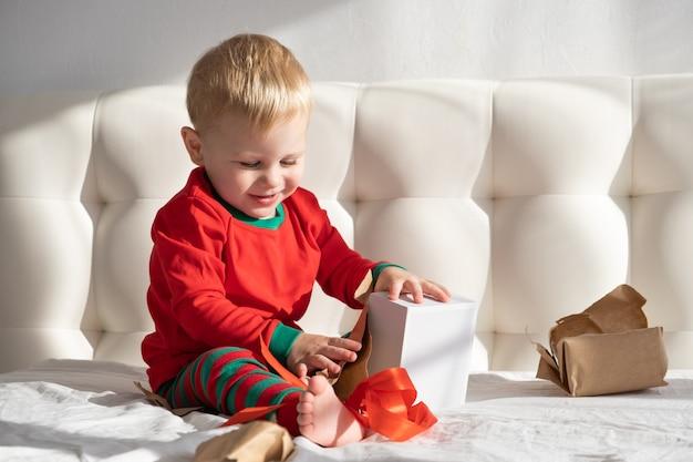 Kleinkindjunge im roten anzug, der geschenkbox öffnet, sitzt auf weißem bett zu hause.