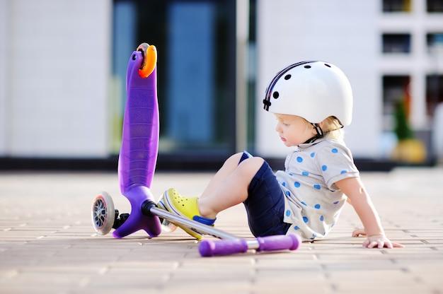 Kleinkindjunge im schutzhelm lernend, roller zu reiten