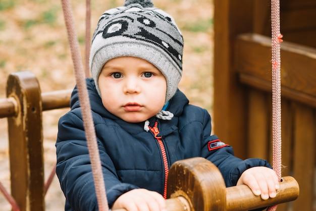 Kleinkindjunge in der warmen kleidung, die im park schwingt