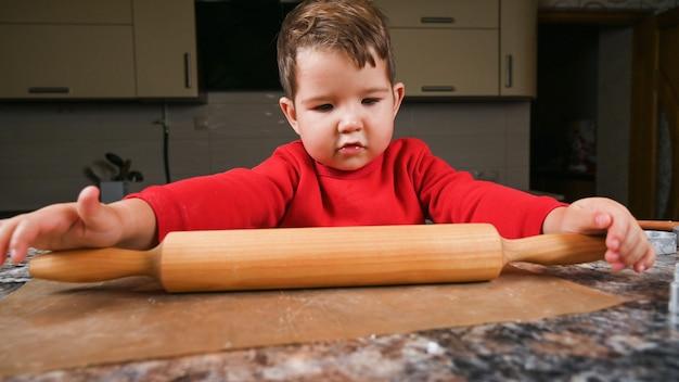 Kleinkindjunge lernt, den teig mit einem nudelholz zu rollen