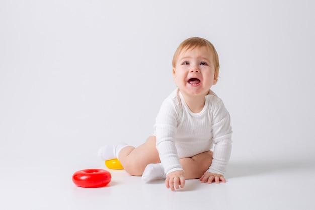 Kleinkindjunge mit spielzeug auf weißem hintergrund