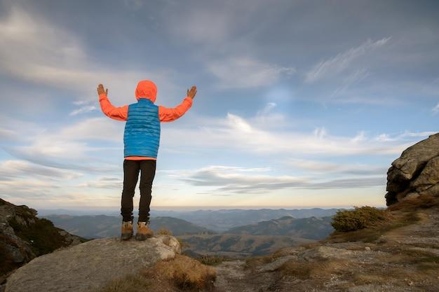 Kleinkindjungenwanderer, der mit erhöhten händen in den bergen steht, die ansicht der erstaunlichen berglandschaft bei sonnenuntergang genießen.