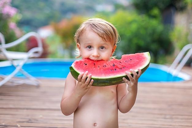 Kleinkindkind, das wassermelone nahe schwimmbad während der sommerferien isst. kinder essen obst im freien.