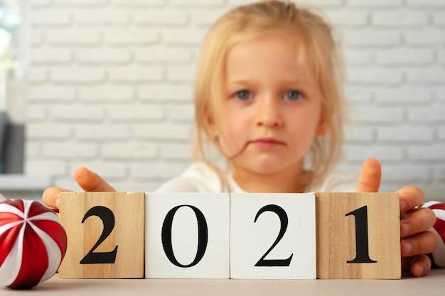 Kleinkindmädchen, das 2021 holzwürfel hält. konzept des neuen jahres 2021
