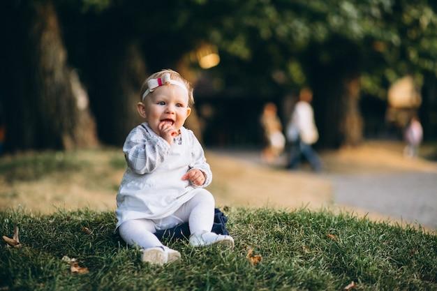 Kleinkindmädchen, das auf gras im park sitzt