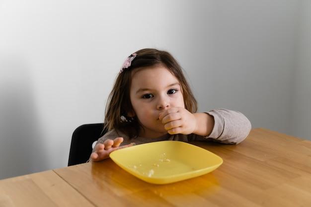 Kleinkindmädchen, das brot oder kuchen zu hause mit ihren händen isst. hungriges kind. ungesunde diät. schlechter tisch
