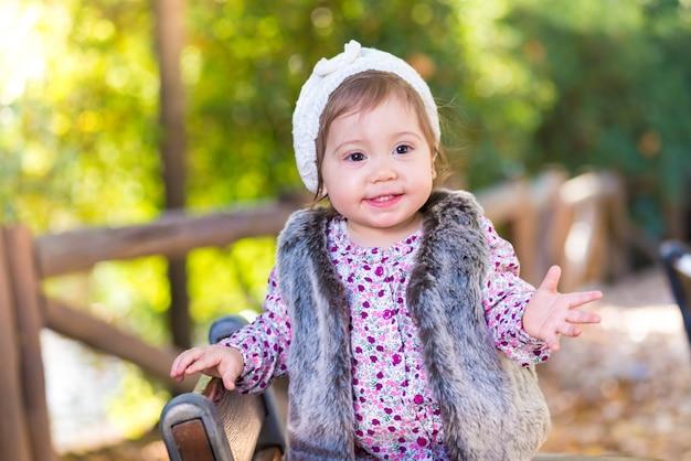 Kleinkindmädchen, das in einem stuhl steht und draußen lächelt.