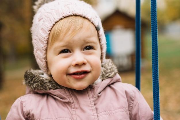 Kleinkindmädchen im herbstpark, der voran schaut