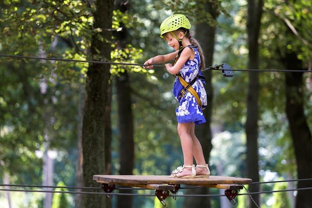 Kleinkindmädchen im sicherheitsgurt und sturzhelm befestigt mit karabiner, um auf seilweise im park zu verkabeln.