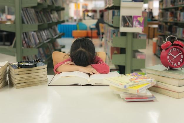 Kleinkindmädchen mit büchern schläft auf bibliotheksschreibtisch