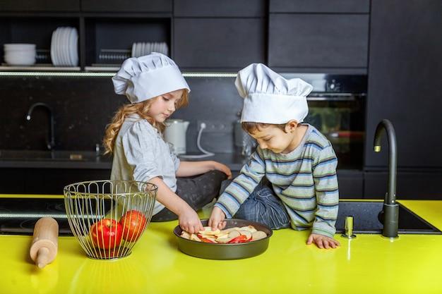 Kleinkindmädchen und -junge mit dem chefhutvorbereiten backen selbst gemachten apfelkuchen in der küche