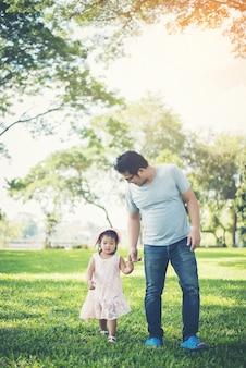 Kleinkindmädchenhändchenhalten mit ihrem vater im park, glückzeit.