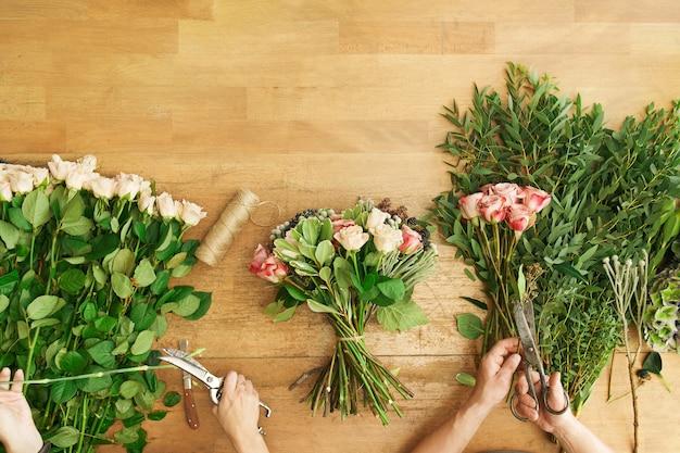Kleinunternehmen. blumen lieferung draufsicht. floristen schaffen ordnung, machen rosenstrauß im blumenladen.