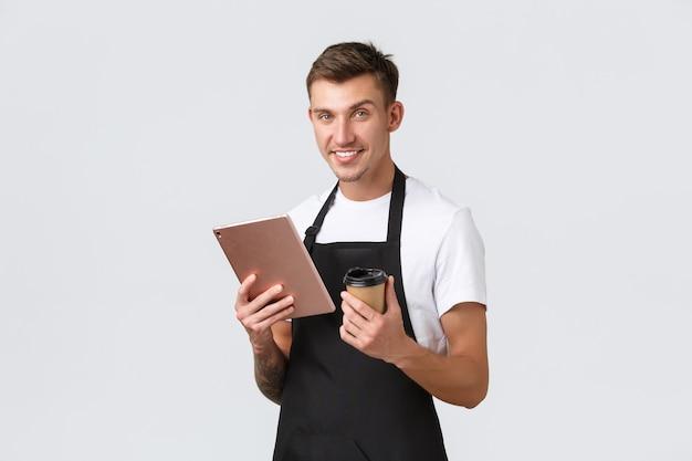 Kleinunternehmen-café-café und restaurants-konzept hübscher lächelnder barista-kellner im schwarzen apr...