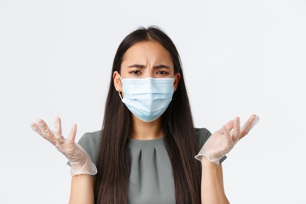 Kleinunternehmer, die das konzept der virenbekämpfung verhindern. frustrierte wütende und verwirrte asiatische frau in medizinischer maske und handschuhen, die achselzuckend die hände hochhob, verwirrt, verstehe nicht