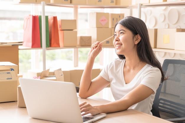 Kleinunternehmer, frau, die bestellung im laptop prüft