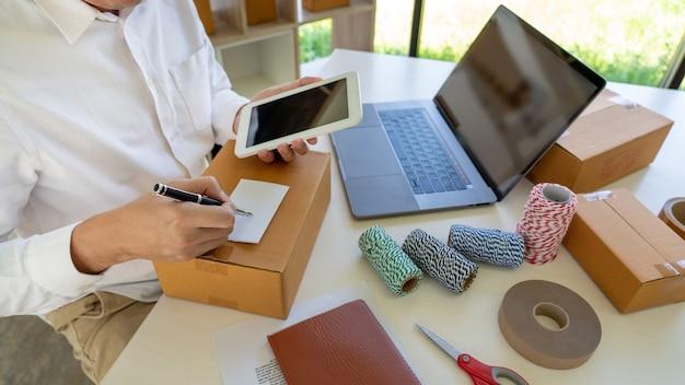 Kleinunternehmer kmu, junger asiatischer mann, der mit laptop-computer und lieferverpackungsbox arbeitet