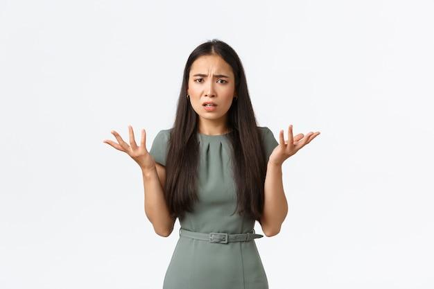 Kleinunternehmer, startup und work from home-konzept. was ist das problem. verwirrte und verärgerte asiatische frau kann nicht verstehen, was passiert ist, zuckte mit den schultern und hob bestürzt die hände, runzelte ratlos die stirn