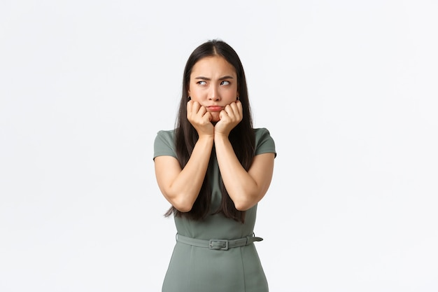 Kleinunternehmer, unternehmerinnenkonzept. schmollende launische asiatische freundin, die sich kindisch verhält, als ob sie links beleidigt aussieht, über streit oder konfrontation mit ihrem freund schmollend, weißer hintergrund