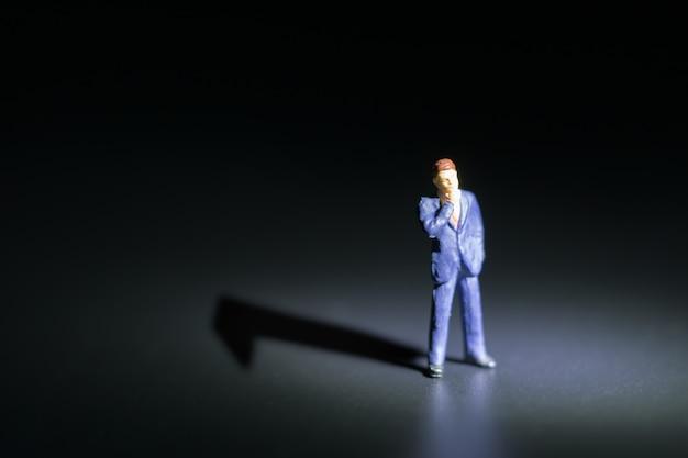 Kleinunternehmerfigur, die mit nummer eins-schatten auf schwarzen hintergründen steht.
