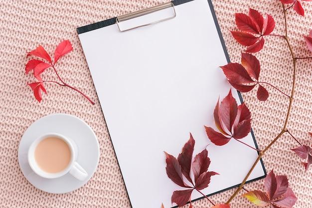 Klemmbrett, herbstlaub und tasse kaffee mit milch auf pastellrosa gestricktem plaid