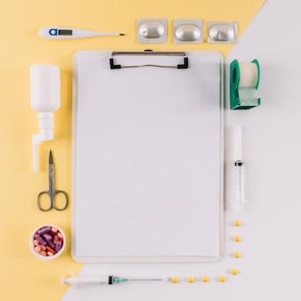 Klemmbrett mit dem leeren Weißbuch umgeben durch medizinische Ausrüstungen auf doppeltem farbigem Hintergrund