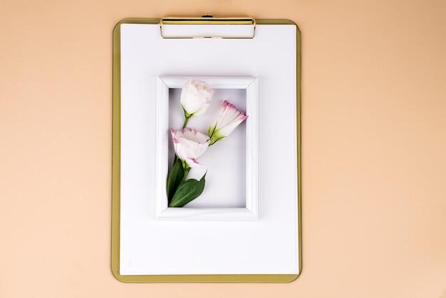 Klemmbrett mit eustomablumen und weißem rahmen