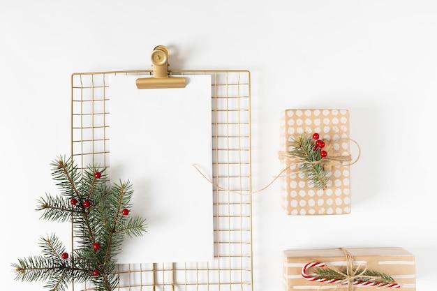 Klemmbrett mit geschenkboxen auf weißer tabelle