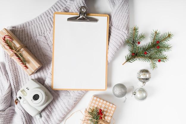 Klemmbrett mit geschenkboxen und grünen zweigen