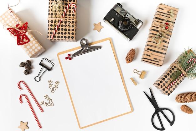 Klemmbrett mit geschenkboxen und kamera auf weißer tabelle