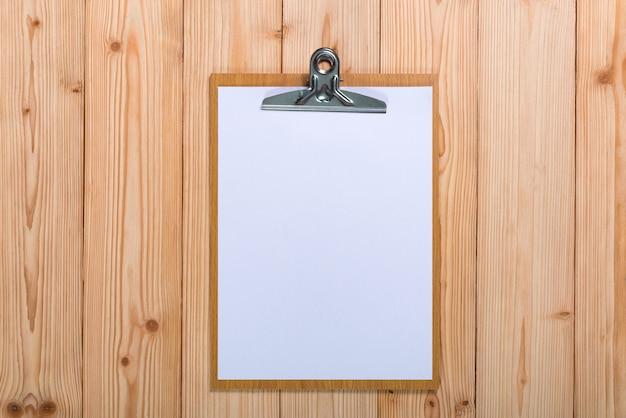 Klemmbrett mit leerem weißbuchblatt auf holz