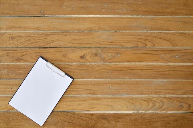 Klemmbrett mit weißem blatt auf hölzernem hintergrund