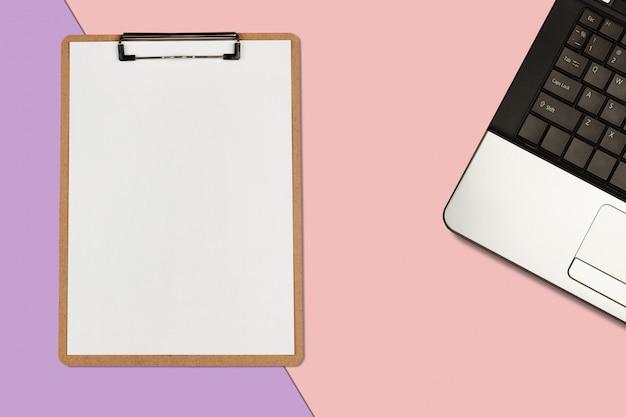 Klemmbrett mit weißem blatt und laptop auf pastellfarbhintergrund