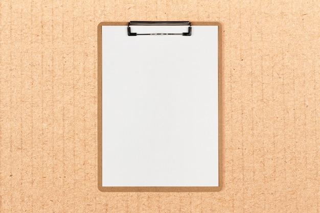 Klemmbrett mit weißem blatt und platz für text auf kraftpapierhintergrund