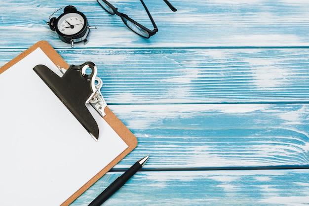 Klemmbrett mit weißem leerem papier auf blauem holztisch, draufsicht