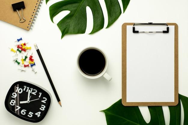 Klemmbrett und weißbuch auf weißem schreibtischhintergrund. flaches lay-design.