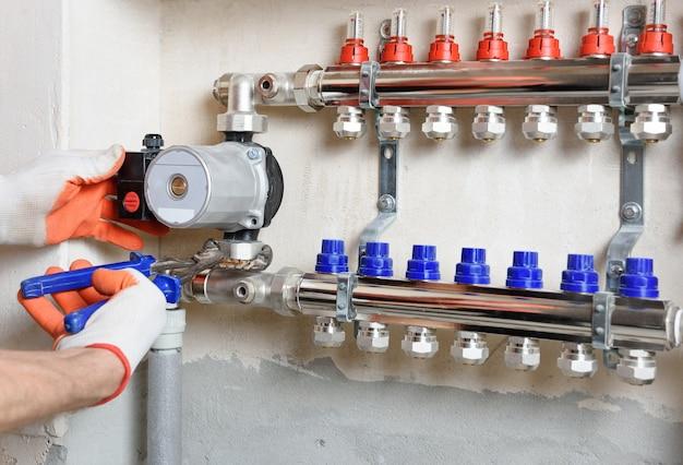 Klempner, der eine wasserpumpe in einem fußbodenheizungssystem repariert