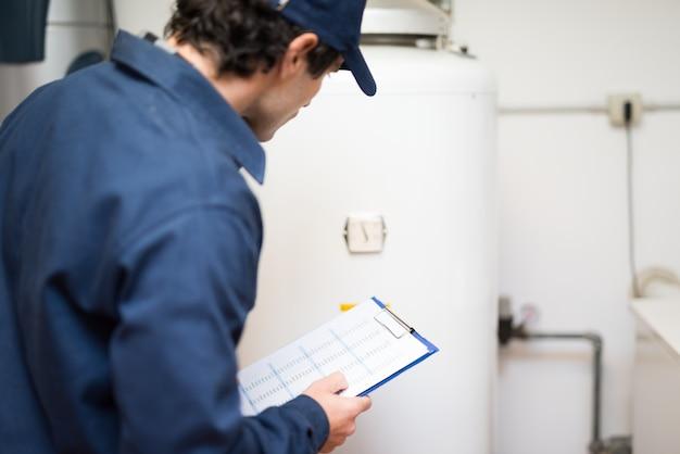 Klempner, der einen heißwasserbereiter repariert