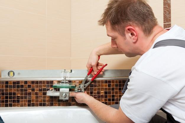 Klempner, der einen mischerhahn in ein badezimmer installiert