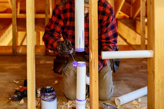 Klempner, der im arbeitsbereich klebstoff auf das pvc-abflussrohr aufträgt.