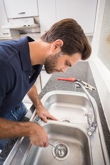 Klempner, der wanne mit schraubenzieher in der küche repariert