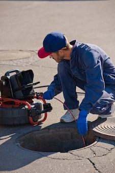 Klempner diagnostiziert einen abflussbrunnen auf der straße mit speziellen geräten.
