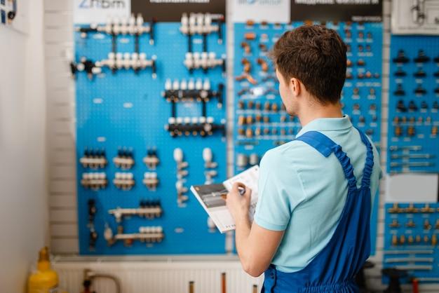 Klempner in uniform am schaufenster mit ventilen und rohrausrüstung im klempnergeschäft. mann mit notebook kauft sanitärtechnik im shop
