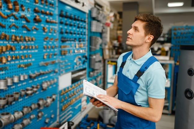 Klempner in uniform an vitrine mit ventilen und rohradaptern im klempnergeschäft. mann mit notebook kauft sanitärtechnik im shop