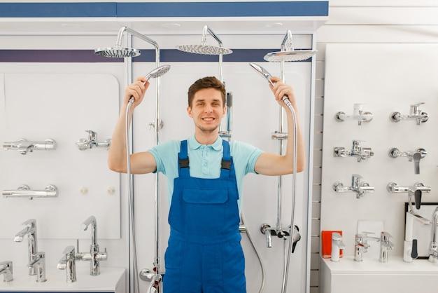 Klempner in uniform, der dusche im schaufenster im klempnergeschäft wählt. mann kauft sanitärtechnik im shop, wahl der badausstattung