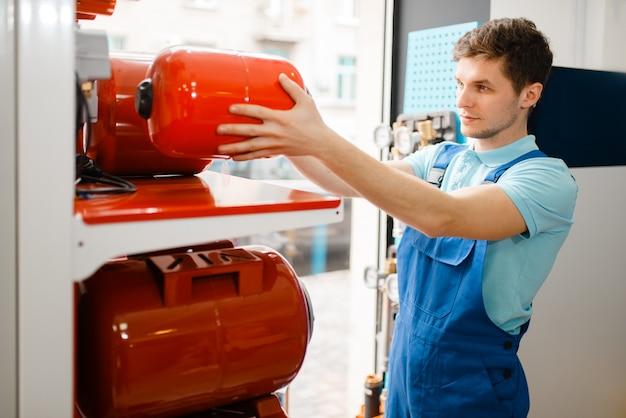 Klempner in uniform, der expansionsbehälter für wasserpumpe am schaukasten im klempnergeschäft wählt. mann kauft sanitärtechnik im shop