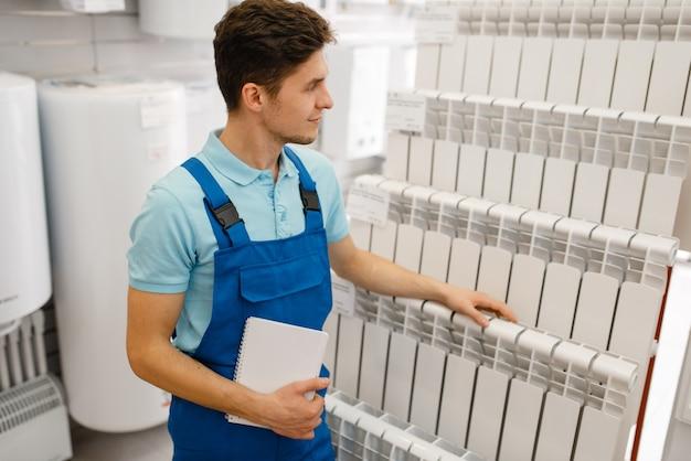 Klempner in uniform, der wasserheizkörper im schaufenster im klempnergeschäft wählt. mann kauft sanitärtechnik im shop